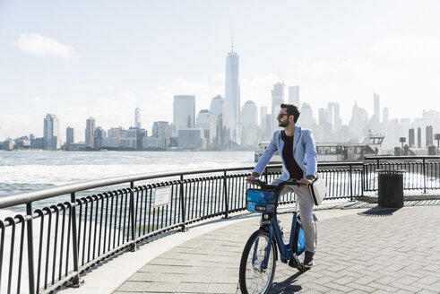 USA, man on bicycle at New Jersey waterfront with view to Manhattan - UUF09719