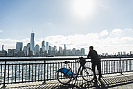 USA, man with bicycle at New Jersey waterfront with view to Manhattan - UUF09722
