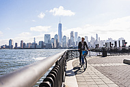 USA, man on bicycle at New Jersey waterfront with view to Manhattan - UUF09728