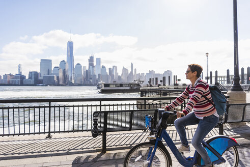USA, woman on bicycle at New Jersey waterfront with view to Manhattan - UUF09731