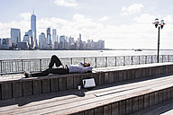 USA, man resting at New Jersey waterfront with view to Manhattan - UUF09740