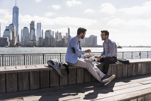 USA, two businessmen working at New Jersey waterfront with view to Manhattan - UUF09743