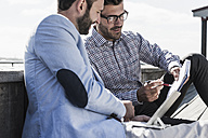 Two businessmen with notepad and tablet working outdoors - UUF09746