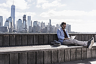 USA, man wearing headphones using tablet at New Jersey waterfront with view to Manhattan - UUF09749