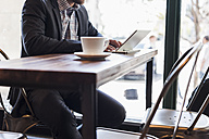 Close-up of businessman using tablet in a cafe - UUF09752