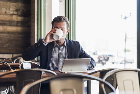 Businessman drinking coffee and using tablet in a cafe - UUF09755