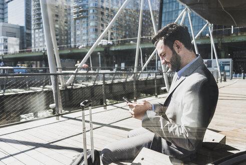 USA, New York, businessman using cell phone - UUF09764