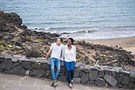 Young couple sitting on stone wall at the coast - SIPF01254