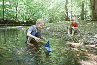 Two boys playing with a toy boat in a forest brook - RBF05528