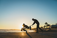 Man walking with a stroller on the seashore at sunset - GEMF01365