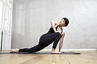 Woman practising yoga - FMKF03450
