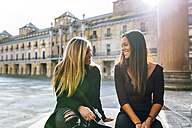 Two smiling young women talking on urban square - MGOF02752