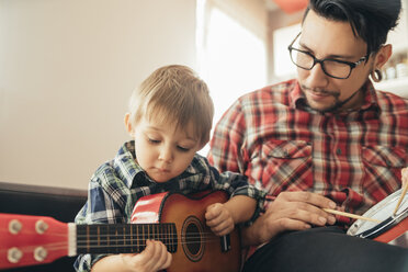 Father and son playing toy musical instruments - ZEDF00480