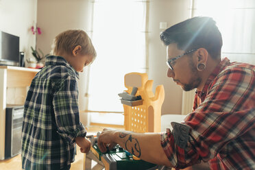 Father and son playing together on toy work bench - ZEDF00486