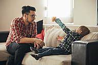 Father and son playing together on couch - ZEDF00489