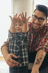 Proud son showing painted tattoos on his hands - ZEDF00495
