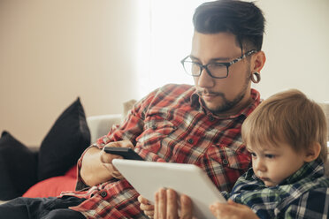 Father and son on couch using tablet and cell phone - ZEDF00501