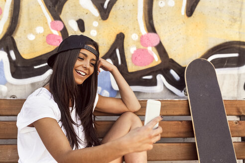 Smiling young woman with skateboard looking at cell phone - MGOF02765