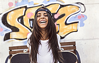 Laughing young woman holding skateboard - MGO02768