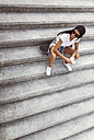 Young woman with skateboard sitting on stairs looking around - MGOF02771