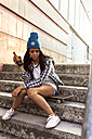 Young woman sitting on skateboard holding a beer bottle - MGOF02777