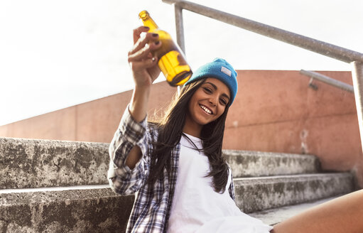 Smiling young woman sitting on stairs holding a beer bottle - MGOF02780