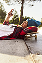 Young woman lying on skateboard looking at cell phone - MGOF02783
