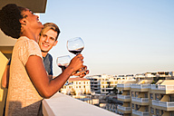 Happy young couple drinking wine on balcony - SIPF01255