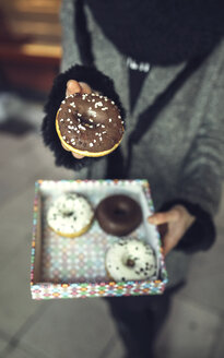 Woman holding doughnut with chocolate icing, partial view - DAPF00534