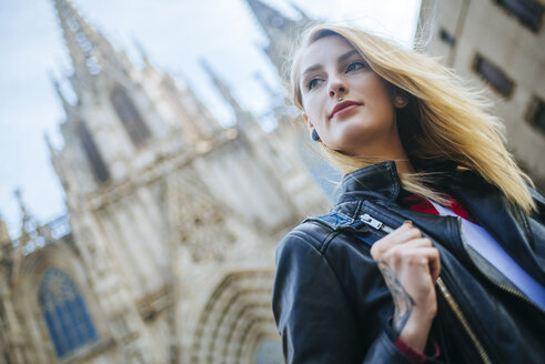 Spain, Barcelona, portrait of young woman with cathedral in the background - KIJF01040