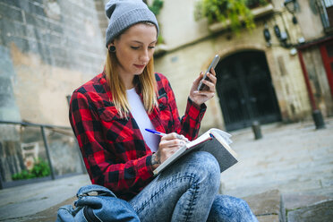Spain, Barcelona, young woman with cell phone sitting on stairs writing in notebook - KIJF01055