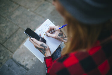 Tattooed woman's hand writing in notebook - KIJF01058