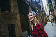 Spain, Barcelona, portait of smiling young woman with camera at Gothic Quarter - KIJF01061