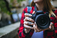 Tattooed woman's hands holding  reflex camera, close-up - KIJF01064