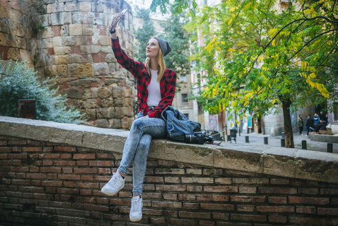 Spain, Barcelona, young woman sitting on a wall taking selfie with cell phone - KIJF01067