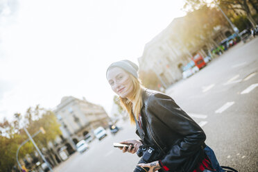 Spain, Barcelona, smiling young woman with mobile phone on the street - KIJF01073