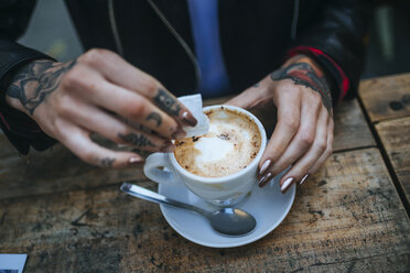 Woman's tattooed hands pouring sugar into cup of coffee, close-up - KIJF01076