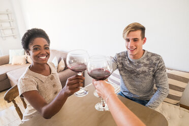 Young couple toasting with red wine at home - SIPF01275