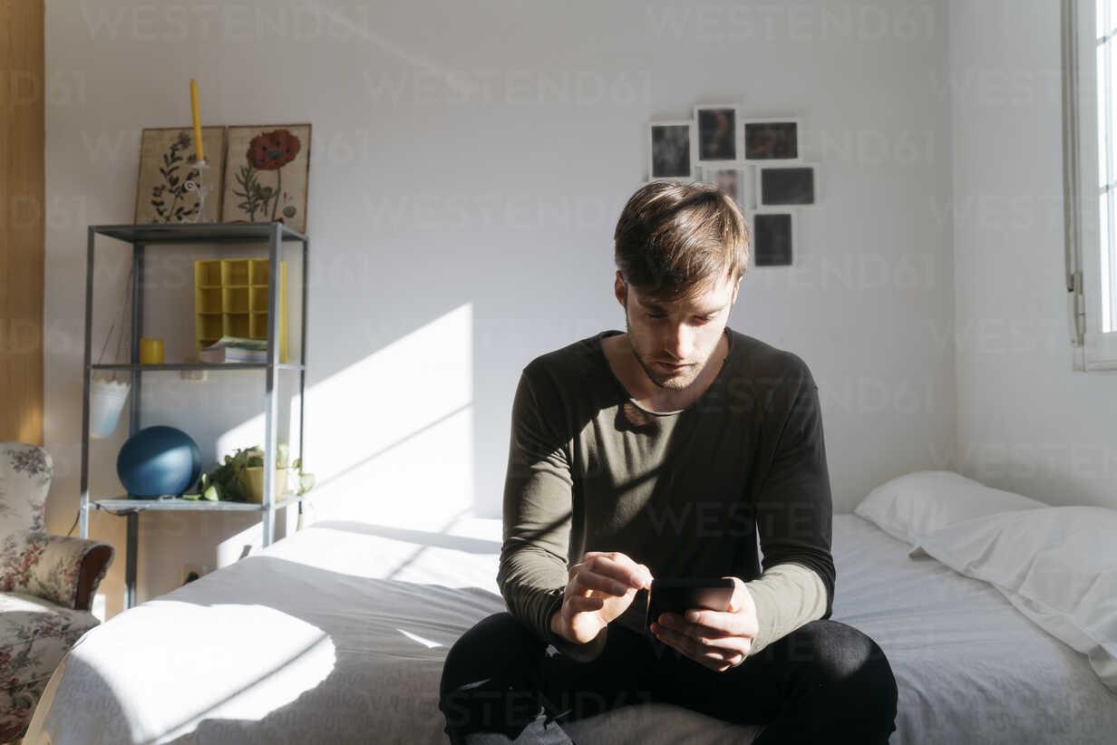 Young man sitting on bed looking at his smartphone - KKAF00290 - Kike Arnaiz/Westend61