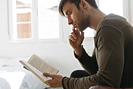 Young man reading book at home - KKAF00293