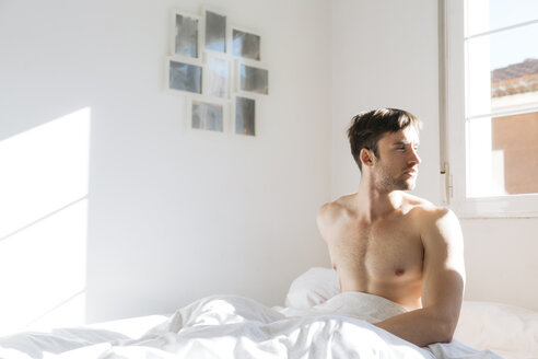 Young man sitting in bed - KKAF00296