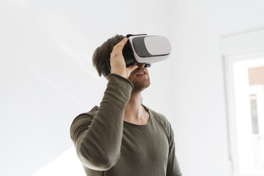 Young man wearing virtual reality glasses at home - KKAF00299