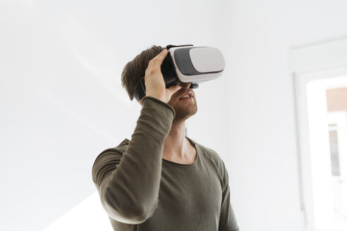 Young man wearing virtual reality glasses at home - KKAF00299