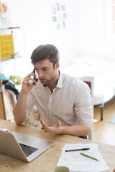 Young man on the phone working from home with laptop - KKAF00302