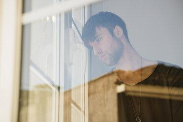 Sad young man looking through window - KKAF00308