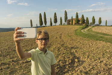 Italy, Tuscany, Boy taking pictures of landscape - PAF01748