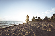 USA, Florida, Key West, woman walking on the beach at sunset - CHPF00361