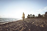USA, Florida, Key West, woman walking on the beach at sunset - CHPF00361