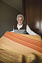 Senior woman putting fresh sheets on a bed - RAEF01644