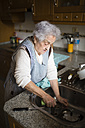 Senior woman washing dishes in kitchen - RAEF01647